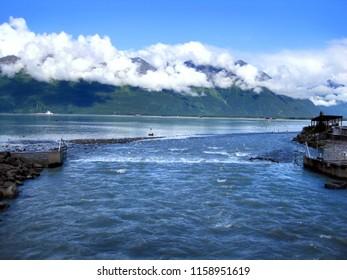 Chugach Mountains surround the Solomon Gulch Fish Hatchery in Valdez, Alaska.  Water and fish channel through the Fish Weir next to the hatchery.