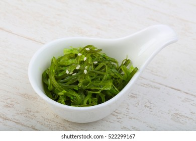 Chuka with sesame seeds in the bowl on wood background