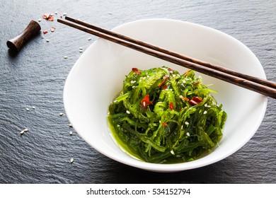 Chuka wakame, seasoned sesame seaweed japanese salad in white bowl and chopsticks on black stone.