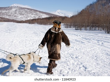 chukchi in national gown leads harness with dog
