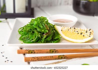 Chukka seaweed salad with peanut sauce, lemon and roasted sesame seeds. Sea vegetable salad with soy sauce. Japanese food.