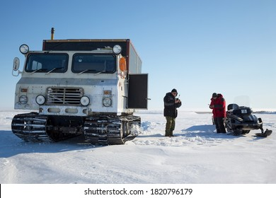 Chukotka, Russia - April 6, 2014. Tracked all-terrain vehicle, snowmobile and two men in the Arctic. Men get in touch on satellite phones. Expeditions and travels to the extreme North of Russia.
