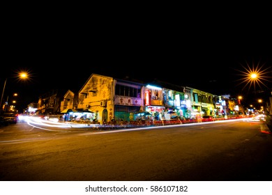 Chulia Street, George Town, Penang, Malaysia - November 4, 2015: A night view of Chulia Street in Penang Malaysia with cars and people passing by in a long shutter exposure.