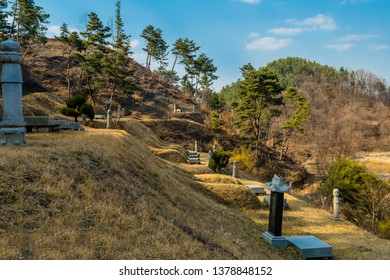 Chungju, South Korea; April 03, 2019: Burial mounds in small graveyard on side of mountain under ble sky.