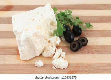 Chunk of Feta Cheese with crumbles and black olives and cilantro  on a wooden board