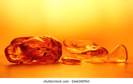 Chunks of amber in the yellow background light. An abstract pattern. Close up, blurred background. Selective focus, emphasis on the left stone. Negative space. Beautiful background, wallpaper.