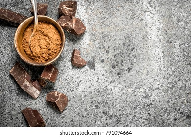 Chunks of chocolate with cocoa powder. On a rustic background.