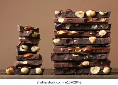 Chunks of chocolate with nuts on a wooden table on a brown