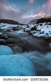 Chunks of ice in the foreground as the white river runs towards Mount Hood in Oregon during sunset with clouds sweeping through the landscape.