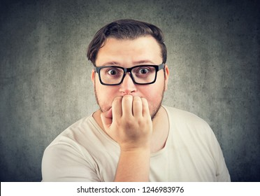 Chunky adult man in glasses biting nails being in panic and anxiety looking at camera