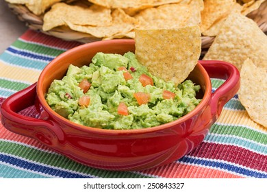 Chunky homemade guacamole in red ceramic dish with corn chips