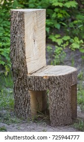 Chunky ugly chair made of the whole tree trunk is standing outdoor on the ground. Unfocused green forest background.