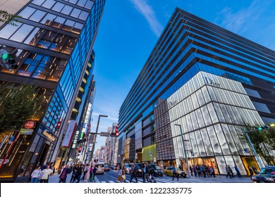 """CHUO, TOKYO / JAPAN - OCTOBER 22 2018 : Evening scenery of Ginza 6-chome in Tokyo. Many tourists visit in an area where luxury shops are lined up. """"GSIX"""" of a commercial facility is a landmark."""