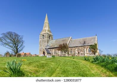 The Church of All Saints in Appleton, East Yorkshire.  The church has a spire and is set during Spring with daffodils in the foreground.  A blue sky is above.