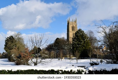 A church among trees with snow on the ground in England