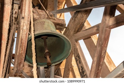 Church bell on the rafters of the bell tower.