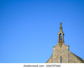 Church bell silhouetted against a bright blue sky