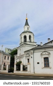 Church with bell tower located on small old town street. White monastery building outdoors on narrow city street