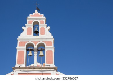 Church bell tower with three bells on blue sky with copy-space