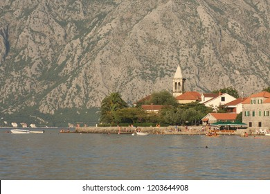 A church in Boka Kotorska bay with majestic mountains in the background and swimmers on the beach in the foreground.