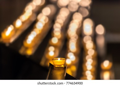 Church candles. Christmas candles or memorial candle or ceremony candle burning in the church. Abstract candles background with a golden light of candle flame. Concept: religion