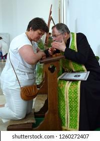 In a church. Catholic priest take a confession from a female parishioner. Ukraine, Kiev, May 5, 2017