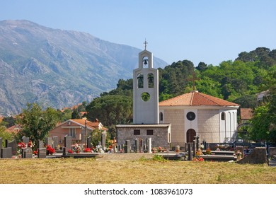 Church with churchyard against mountains. Montenegro, Orthodox church of St. Peter of Cetinje ( Svetog Petra Cetinjskog ) in Prcanj town