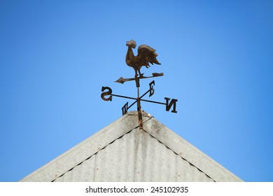 A church cockerel on a tin roof with a beautiful clear blue sky as background.