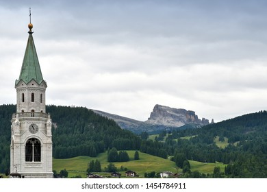 The Church of Cortina d'Ampezzo with Cinque Torri Dolomitic group on the background (Sexten Dolomites). Veneto Italy, Europe.