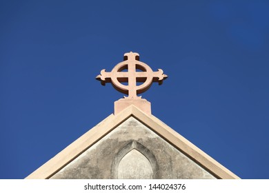 Church cross against plain blue sky