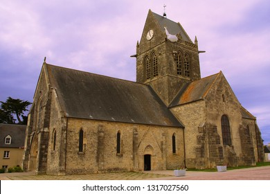 Church of Sainte-Mère-Église, with a doll hanging on the spire of the church of the city, in the shape of an American parachutist. Symbol to remember what happened on D-Day in Normandy, world war II.
