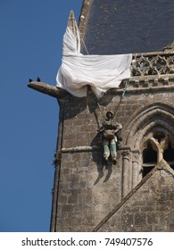 church in Sainte-Mère-Église, with the drawning of a paratrooper  with a parachute and doll caught on the spire of the town church to remember what happened during D-day in Normandy, world war 2