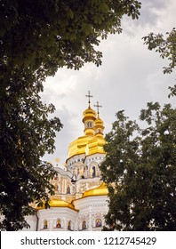Church with golden domes at Kiev Pechersk Lavra Christian complex against blue sky. Old historical architecture in Kiev, Ukraine