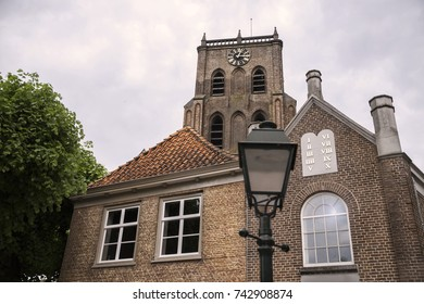 A church and historical architecture with a house and synagogue in an old street in the Netherlands