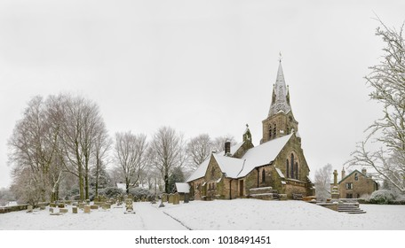 The Church of the Holy and Undivided Trinity, Edale, Peak District, Derbyshire, England, UK. Snow covered Winter landscape at Christmas. Copy space over blank sky for festive text.