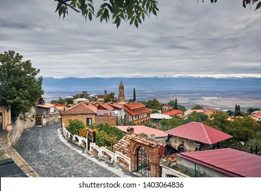 Church and houses at the street of Signagi town with Alazani valley and mountains at background in Georgia