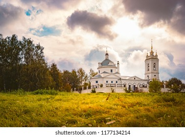 Church in Konstantinovo, Moscow region, Russia. Dramatic sunset cloudy sky in background and meadow in foreground.