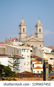 The Church of Lapa at Porto as seen from a distance, amidst various buildings.