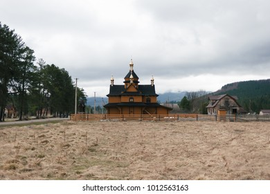 a church made of wood is on a plain that is located in the mountains