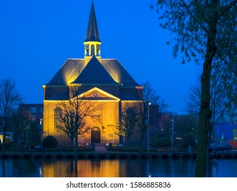 Church named 'Oudhoornse Kerk' in the town of Alphen aan den Rijn, Netherlands is illuminated by light beams during blue hour. Old historic church along the river Rhine.