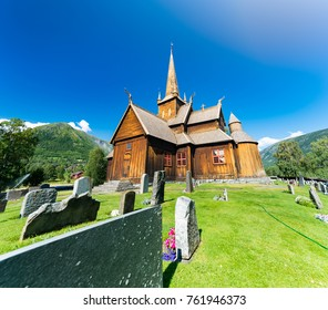 Church in Norway on sunny day with blue cloudy sky in background and green grass and cemetery in foreground
