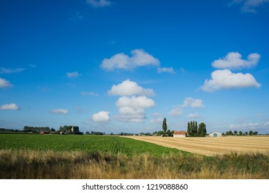 Church of Oeren and farm in Westhoek West Flanders Belgium under big sky with clouds