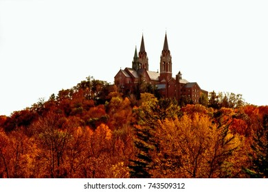 Church On a Hill with golden Fall color, towering over the woods below. Three towers, autumn scenic.