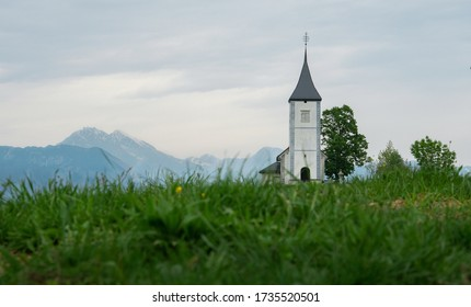 Church on a hill with meadows surrounding it in Jamnik, Slovenia