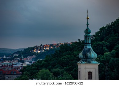 Church of Our Lady Victorious and St. Anthony of Padua (home of the Infant Jesus of Prague). Spire in the foreground of the Petrin trees. Sun setting rays illuminating the Brabenec hill in Radlice.