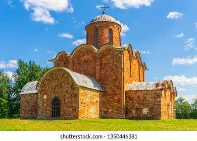 Church of Our Saviour on Kovalev, Velikiy Novgorod vicinity, Russia. Russian landscape, green trees, grass and ancient orthodox temple against blue sky. Beautiful scenery and architectural landmark