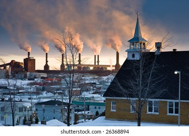 A church overlooking smoke stacks at sunset