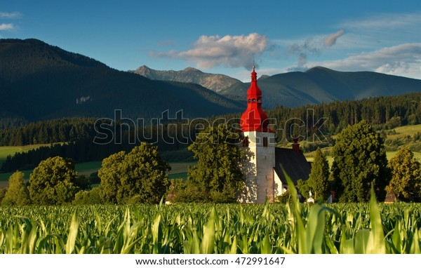 Church with a red roof - Slovak Republic.  Church under high mountains. Corn field with a church.