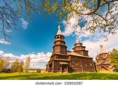 Church in russia on sunny day with blue cloudy sky in background and green grass and cemetery in foreground