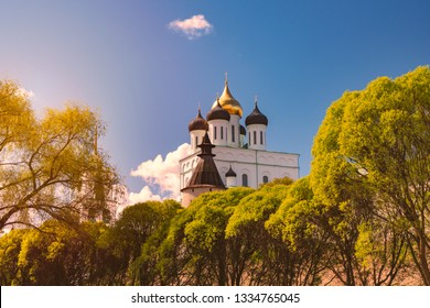 Church in Russia on sunny day with blue cloudy sky in background and green trees in foreground
